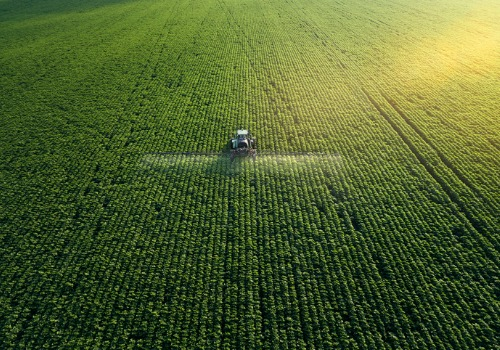 A tractor spreading Fertilizers over a field of crops