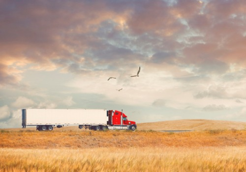 A truck driving alongside a field during Grain Delivery